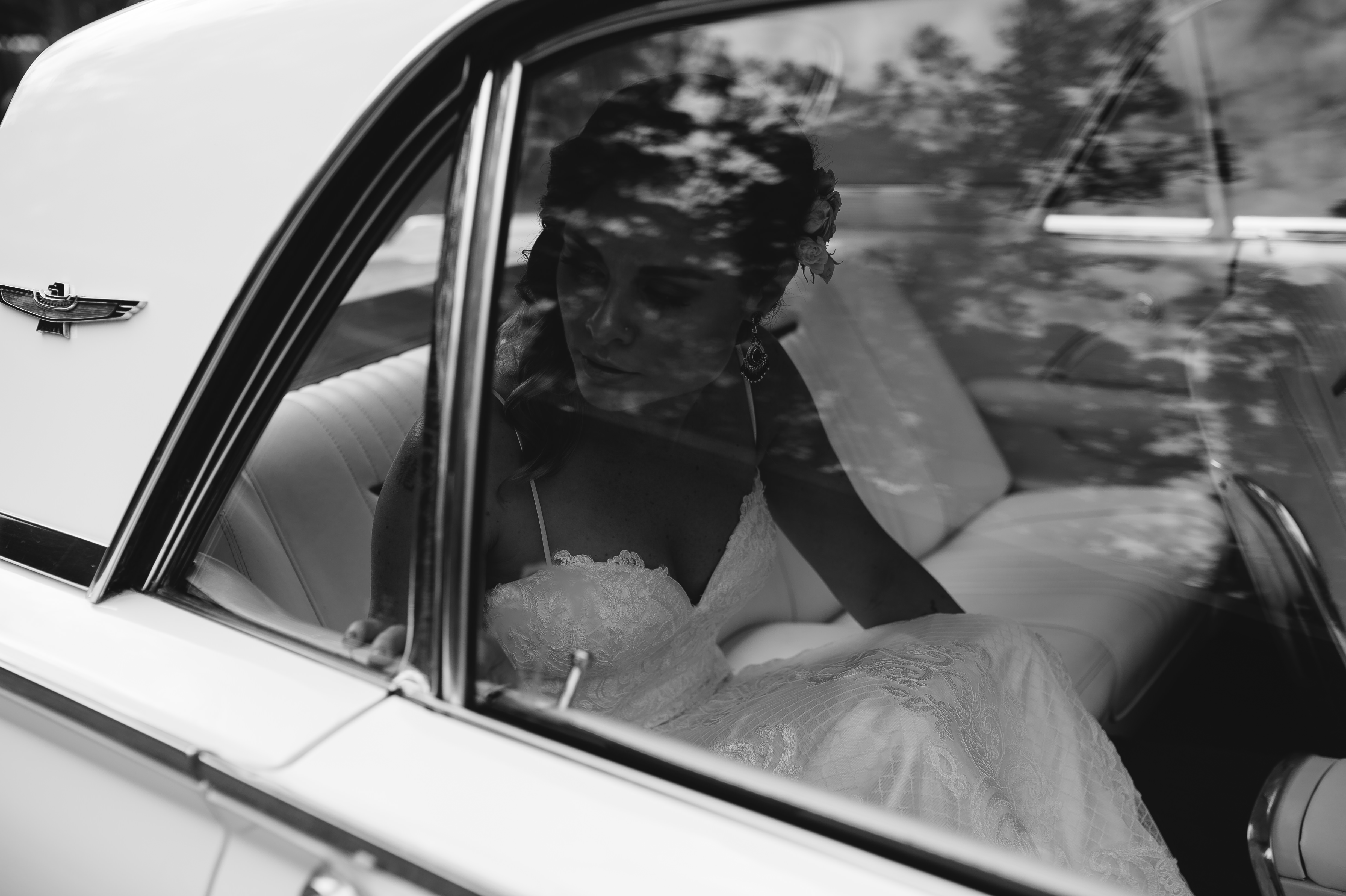 Black and white image of bride sitting in a classic car