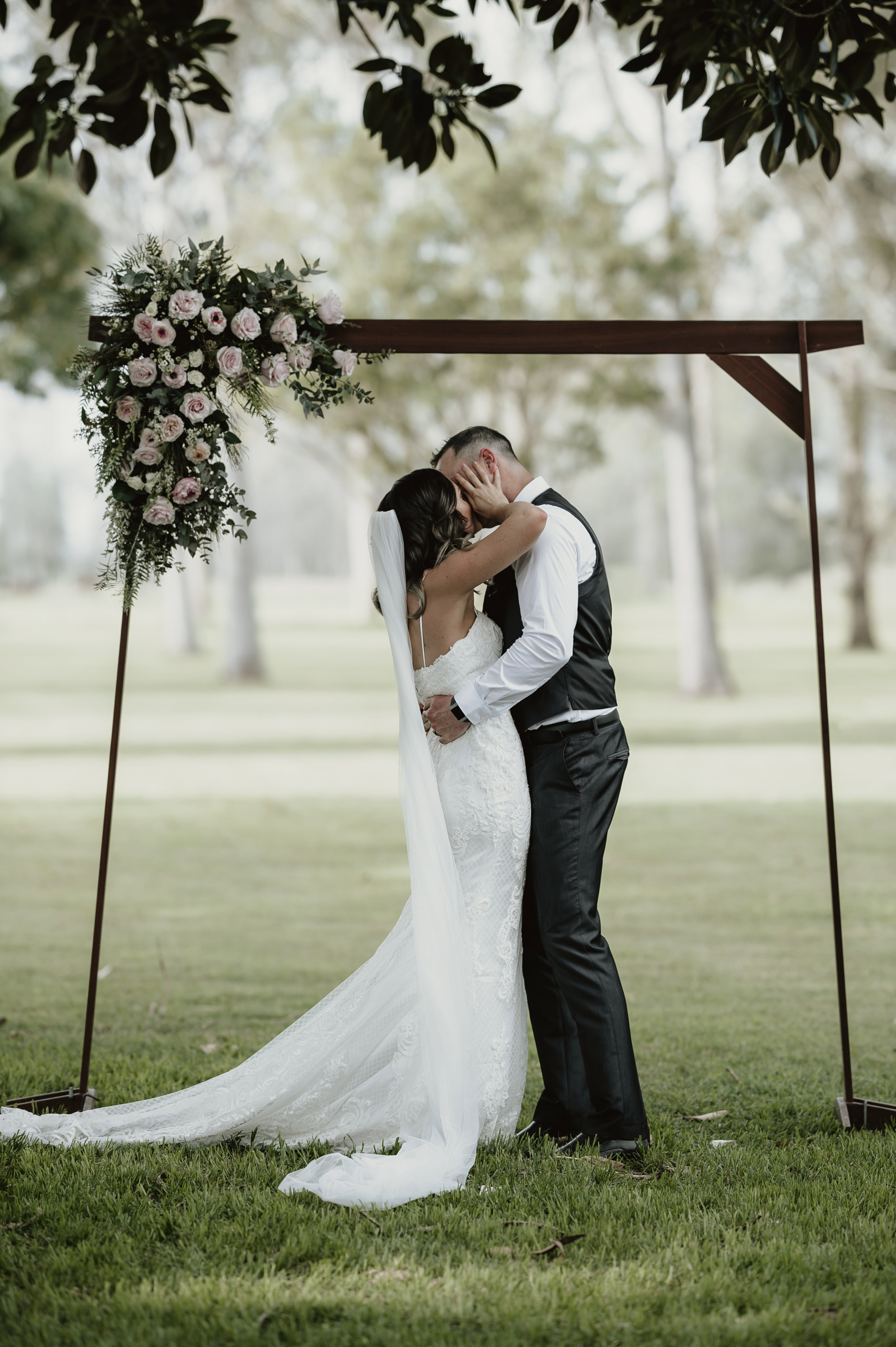 Bride and groom kissing under floral arbor