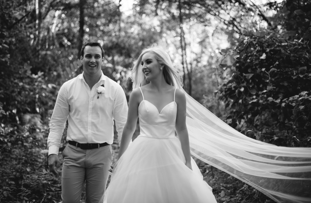 Bride walks through forest with her husband