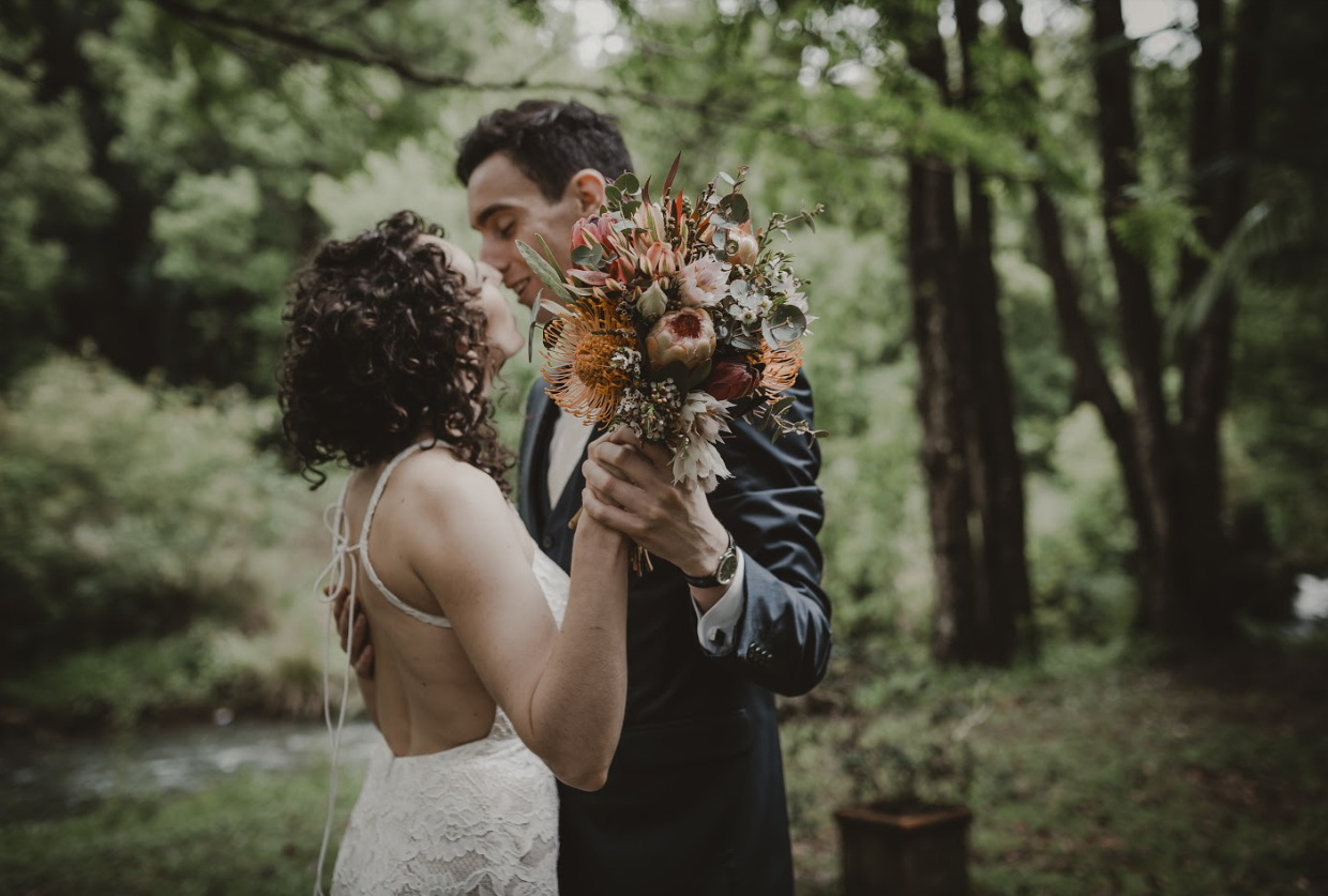 Bride and groom kiss while holding flower bouquet