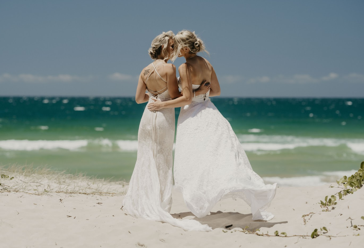 Bride and bride in white dresses kiss at the beach